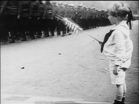 B/W 1918 child waving US flag as soldiers march past in Victory Parade / end of WW