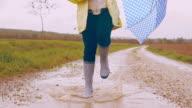 SLO-MO-Kind mit Regenschirm überspringen durch eine Pfütze