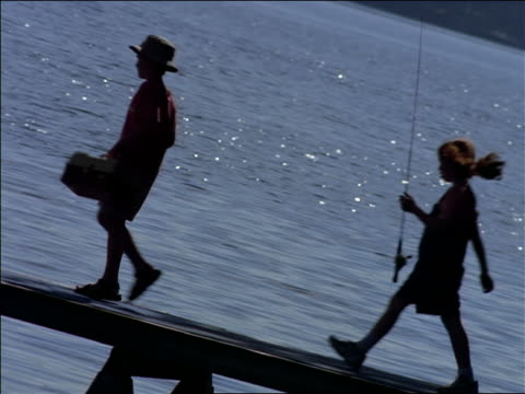 CANTED children + adults carrying fishing rods + tackle boxes walking + sitting down on dock on lake