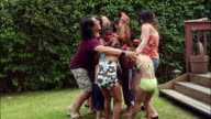 Children and adults standing in group and having water balloon fight on lawn / New Jersey