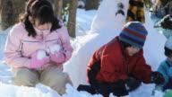MS PAN TU Children (2-11) and mother making snowman / Richmond, Virginia, USA