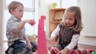 MS DS Children building up pink tower on carpet / Potsdam, Brandenburg, Germany