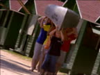 CANTED children carrying canoe over their heads walking next to green cabins toward camera
