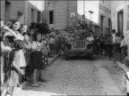B/W 1943 children cheering on village street as GIs drive thru on crowded offroad vehicle/ Sicily / doc