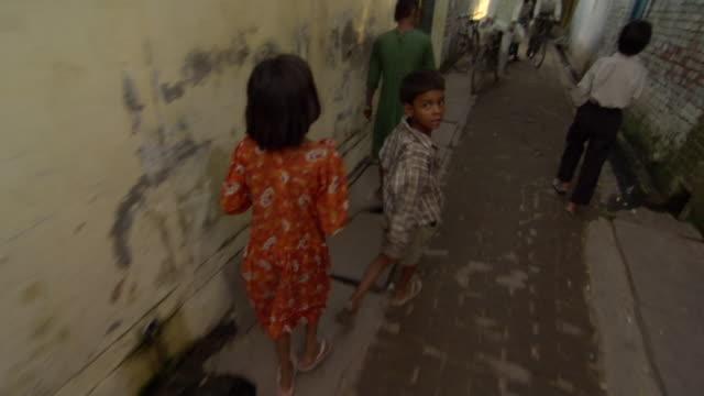 WS TU POV Children, cyclists and man with motorbike in alley, Agra, Uttar Pradesh, India