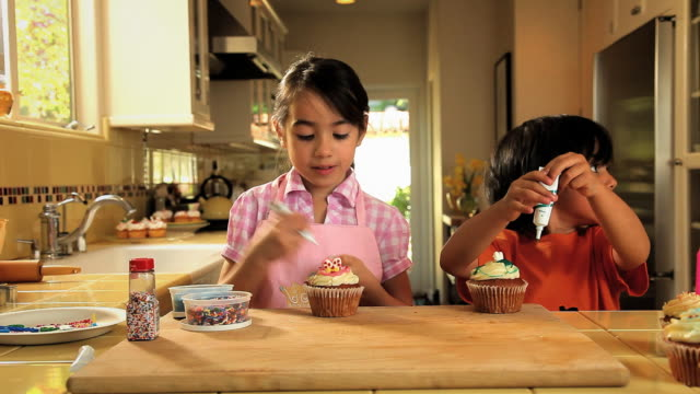 MS Children decorating cupcakes with colored frosting / Los Angeles, California, USA