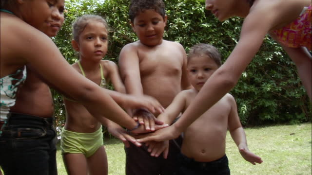 Children dressed in swimsuits standing on lawn and overlapping hands to cheer / New Jersey