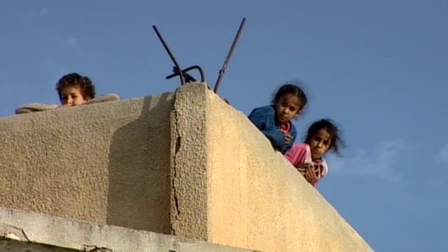Children duck behind a wall as they hear gunshots