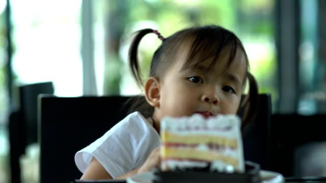 Barn äter glad tårta.