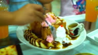 Children eat waffles in a cafe.