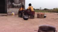 MS Children eating meal sitting outside shack, Tamale, Ghana