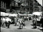 IMMIGRANTS Children gathered around enclosed turning MerryGoRound at Street Fair Street vendors w/ umbrellas over stalls MELTING POT VS Shop signs in...
