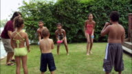 Children having water balloon fight on lawn / New Jersey