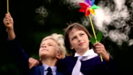 Children holding pinwheel triumphantly in air