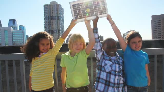 Children holding solar panel on urban rooftop