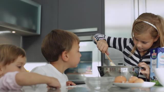 MS Children (2-11) in kitchen, girl (10-11) mixing dough / Kleinmachnow, Brandenburg, Germany