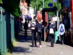 Children in school uniform go to catch red London bus London