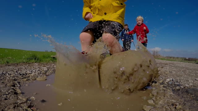 Children Jumping in muddy puddles