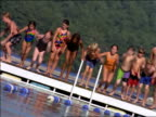 CANTED children jumping off floating platform in middle of lake / pine trees in background