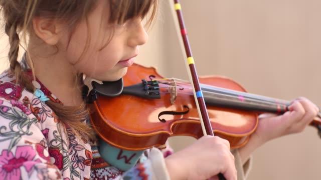 Children learning in Montessori school environment playing violin