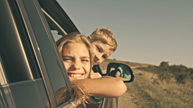 Children looking out car window, smiling at camera