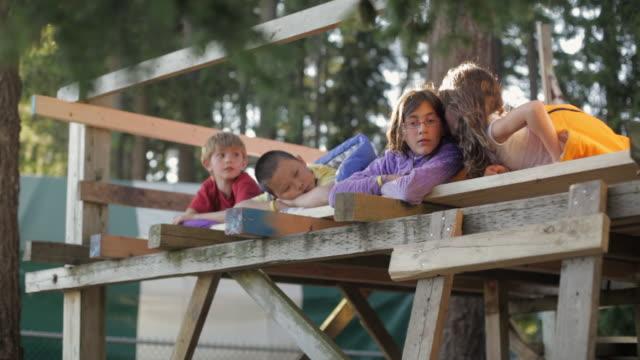 LA Children lying in a tree fort telling secrets / Vancouver, British Columbia, Canada