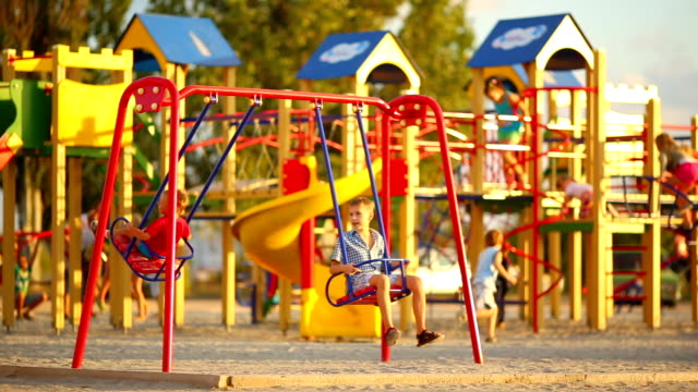 children on the swings at the playground