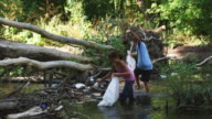 children picking up trash in a river