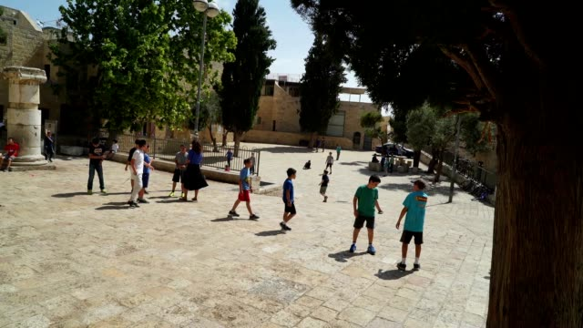 Children play in the Jewish Quarter of the old city near the monument to the War of 1948