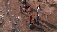 Children play next to an open sewer trough in the slums of Dharavi. Available in HD.