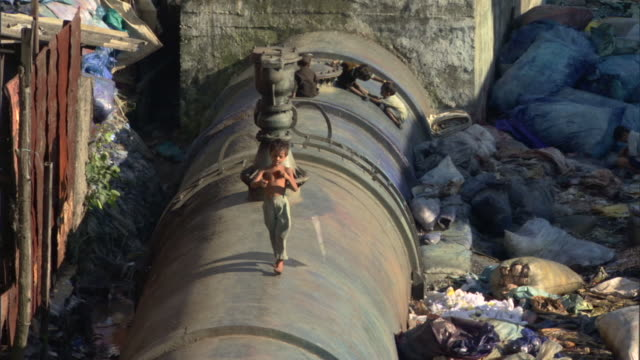 WS ZO HA Children playing and walking on large water pipe amidst trash and garbage in slum, Mumbai, Maharashtra, India