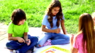 Children playing board game outdoors.
