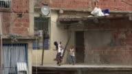 MS ZO WS Children playing on balcony of mountainside slums in Petare / Caracas, Miranda, Venezuela