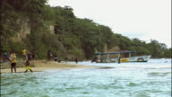 WS Children playing soccer on beach and wading in ocean / Ocho Rios, Jamaica