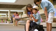 Children playing with cell phone while waiting for baggage at airport