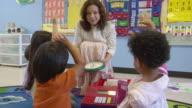 MS Children raising their hands in preschool classroom while teacher calls on them / San Antonio, Texas, USA