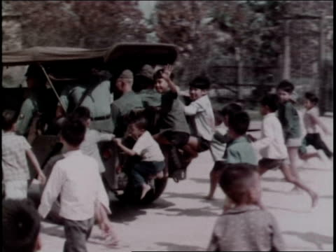 MS children running after and riding on the back of a Jeep / Vietnam
