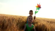 Children running on wheat field
