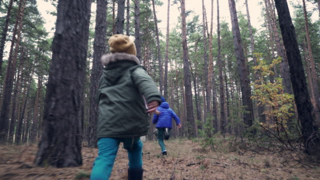 Children running to mother and granny in the forest