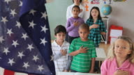 MS HA Children (6-7) saying oath in classroom with American flag in foreground / Jersey City, New Jersey State, USA