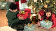 Children shaking Christmas presents by tree