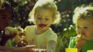 CU PAN Children (2-5) sitting at outside table eating cupcakes / Burbank, California, USA