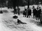 Children sledge down a hill in Alexandra Park