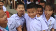 MS SLO MO POV Children standing laughing at schoolyard / Vientiane, Laos