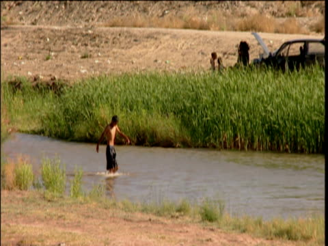 Children swimming in Rio Grande on Mexican side of border with Cuidad Juarez slums behind El Paso Texas USA