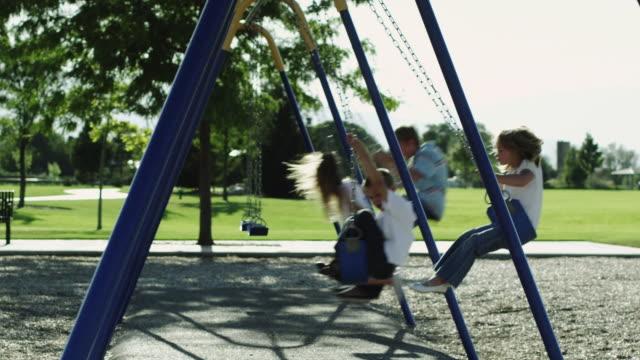 WS PAN SLO MO Children (4-13) swinging on swings in park / Orem, Utah, USA
