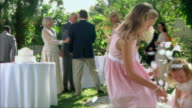 WS Children (6-9) throwing petals at each other, bride and groom thanking guests / Tampa, Florida, USA