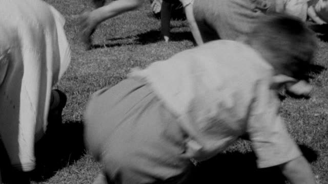1940 MONTAGE Children tumbling and playing during recess at school / United Kingdom