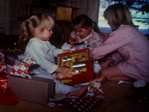 Children unwrap their Christmas presents.