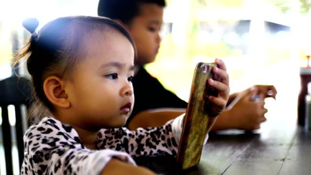 Barn använder telefonen i en restaurang.